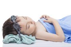 Un muchacho cansado duerme después de jugar en la piscina Foto de archivo libre de regalías