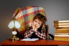 Un muchacho cansado en la tabla con los libros Educación preescolar Fotos de archivo libres de regalías