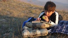 Un muchacho caucásico come una manzana y lee un libro a través de una lupa en los rayos de la puesta del sol metrajes