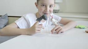 Un muchacho caucásico que juega las marionetas del finger, juguetes, muñecas - las figuras de los animales, héroes del teatro de  almacen de metraje de vídeo