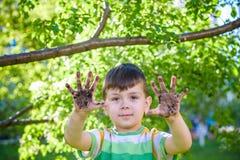 Un muchacho cauc?sico joven que muestra apagado sus manos sucias despu?s de jugar en suciedad y arena imagen de archivo