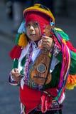 Un muchacho colorido vestido se realiza abajo de una calle de Cusco durante el desfile del primero de mayo en Perú Fotos de archivo libres de regalías