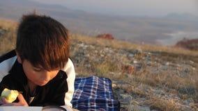 Un muchacho come una manzana y lee un libro a través de una lupa en el fondo de la naturaleza salvaje metrajes