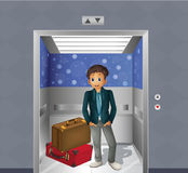 Un muchacho con dos bolsos que viajan dentro del elevador Fotos de archivo libres de regalías