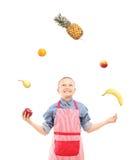 Un muchacho con el delantal que hace juegos malabares con las frutas Foto de archivo libre de regalías