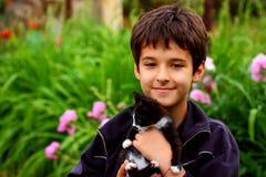 Un muchacho con el gato Imagen de archivo
