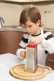 Un muchacho con el rallador Fotos de archivo