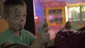 Un muchacho con un hocico pintado del gato en una cara que juega una máquina de juego almacen de video