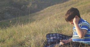 Un muchacho con los auriculares que escucha la música en la naturaleza almacen de video