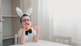 Un muchacho con los oídos del conejito en su cabeza que se sienta en una tabla blanca que come una zanahoria almacen de video