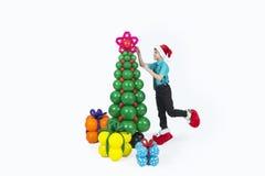 Un muchacho con los regalos del árbol de navidad y de los globos Fotos de archivo