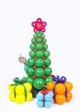 Un muchacho con los regalos del árbol de navidad y de los globos Foto de archivo libre de regalías