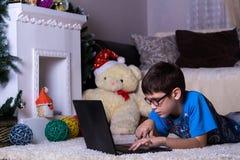 Un muchacho con un ordenador portátil que miente en el piso en casa, en la alfombra Tecnología, Internet, concepto moderno de la  fotos de archivo libres de regalías
