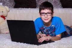 Un muchacho con un ordenador portátil que miente en el piso en casa, en la alfombra Tecnología, Internet, concepto moderno de la  imagen de archivo