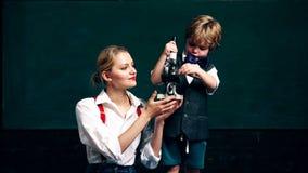 Un muchacho con un profesor mira un microscopio en el fondo de un consejo escolar verde Aprendizaje de concepto Alumnos metrajes