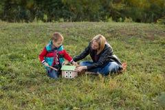 Un muchacho con su madre en el bosque recolectó un DES de madera de la casa Imagen de archivo