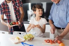 Un muchacho con su padre y abuelo que preparan una ensalada para la acción de gracias Imagenes de archivo