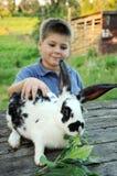 Un muchacho con un conejo en el jardín Fotos de archivo