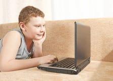 Un muchacho con un ordenador Imagen de archivo libre de regalías