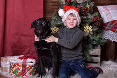 Un muchacho con un perro negro en sombreros de la Navidad Foto de archivo