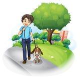 Un muchacho con un perro que camina a lo largo de la calle Fotografía de archivo