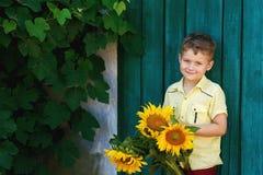 Un muchacho con un ramo de girasoles en un fondo de una puerta vieja Imagen de archivo