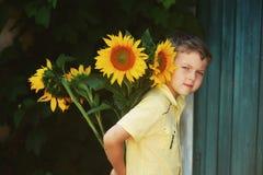 Un muchacho con un ramo de girasoles en un fondo de una puerta vieja Imagen de archivo libre de regalías