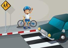 Un muchacho con una bici que se coloca cerca del carril peatonal Foto de archivo