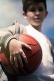 Un muchacho con una bola del baloncesto en el fondo del cielo El concepto de deporte Fotografía de archivo libre de regalías