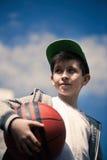 Un muchacho con una bola del baloncesto en el fondo del cielo El concepto de deporte Imagenes de archivo