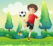 Un muchacho con una camisa roja que golpea un balón de fútbol con el pie Fotografía de archivo libre de regalías