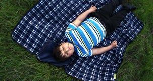 Un muchacho con una cuchilla de la hierba en su boca sueña con el suyo observa cerrado en una manta en un césped verde metrajes