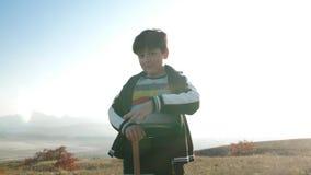 Un muchacho con una espada de madera en el fondo de un paisaje de la montaña almacen de metraje de vídeo