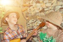 Un muchacho con una guitarra canta a una muchacha con canciones de un lirio de los valles imagen de archivo