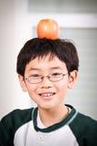 Un muchacho con una manzana Fotos de archivo
