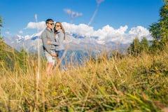 Un muchacho con una muchacha en las montañas en el fondo de las montañas del verano del paisaje rocoso con los árboles el sentars Imagen de archivo libre de regalías