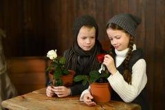Un muchacho con una muchacha en un vestido del vintage que se sienta en un escritorio viejo Mirada de las flores Imagenes de archivo