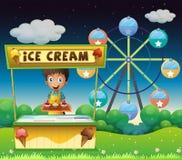 Un muchacho con una parada del helado cerca de la noria Fotografía de archivo