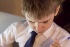 Un muchacho contrariedad piensa en un cuaderno tradicional en una jaula Foto de archivo