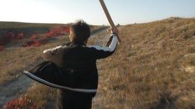 Un muchacho corre abajo de la colina con una espada de madera almacen de metraje de vídeo