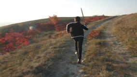 Un muchacho corre abajo de la colina con una espada de madera contra el contexto de un paisaje montañoso almacen de metraje de vídeo