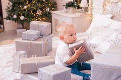Un muchacho de un año se sienta en una cama blanca cerca del árbol de navidad y guarda un regalo Lo visten en una camisa blanca imagenes de archivo