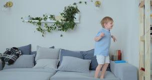 Un muchacho de 4 años con el pelo blanco y los saltos azules y las sonrisas de una camisa en el sofá Diversión y bebé en casa almacen de video