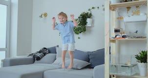 Un muchacho de 4 años con el pelo blanco y los saltos azules y las sonrisas de una camisa en el sofá Diversión y bebé en casa almacen de metraje de vídeo