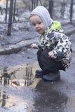Un muchacho de 2 años que juega con un palillo de madera en un charco foto de archivo libre de regalías