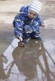Un muchacho de 2 años que juega con una hoja en un charco Fotos de archivo