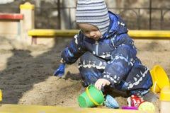 Un muchacho de 2 años que juega en una salvadera Imagen de archivo libre de regalías