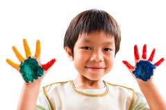 Un muchacho de la guardería de la sonrisa se divierte para pintar su mano con colores Fotos de archivo