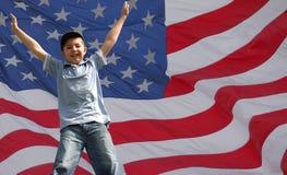 Un muchacho de salto de la estrella delante del indicador de los E.E.U.U. Imagen de archivo