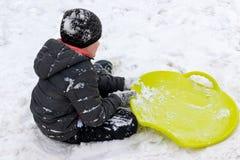 Un muchacho de siete años que se sientan en la nieve y un trineo plástico verde del platillo que miente cerca de él Concepto de a imagenes de archivo